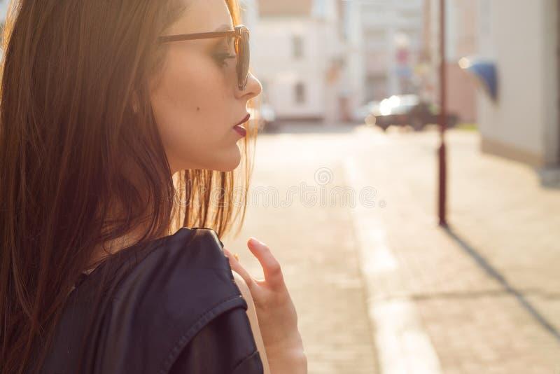Красивая стильная девушка в черной кожаной куртке с солнечными очками с темной губной помадой в городе на заходе солнца стоковые фотографии rf