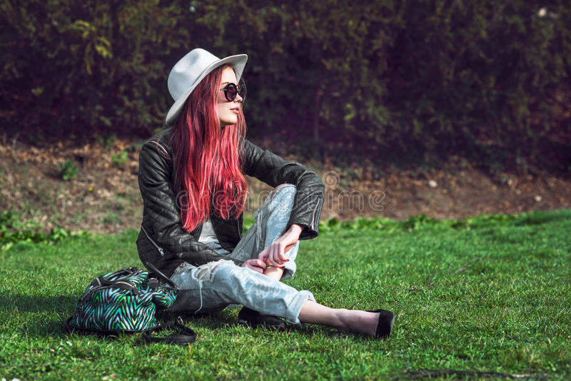 Красивая стильная красная с волосами женщина модели битника моды сидя outdoors на зеленой траве на солнечных очках, шляпе и черно стоковые изображения rf