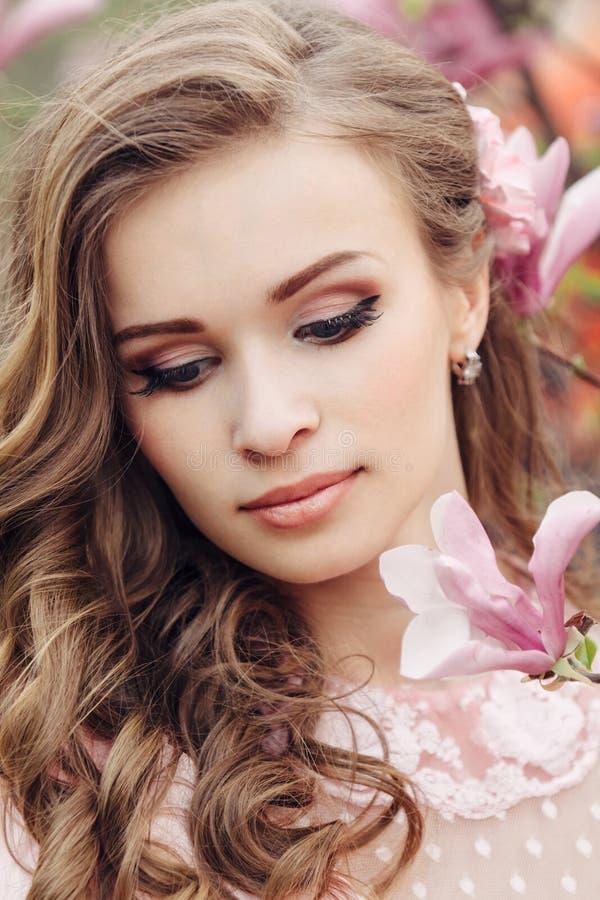 Красивая сторона женщины с розовыми цветками стоковые изображения rf