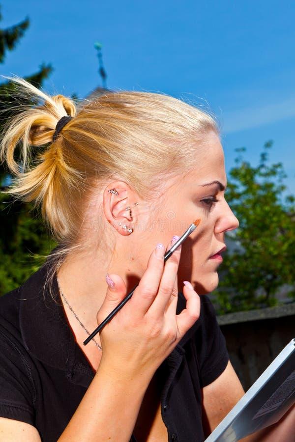 Красивая сторона молодой женщины с прикладывать состав красоты стоковая фотография rf