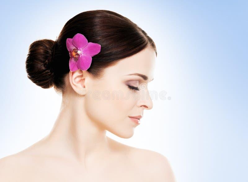 Красивая сторона молодой и здоровой девушки с цветком орхидеи в ее волосах стоковое изображение