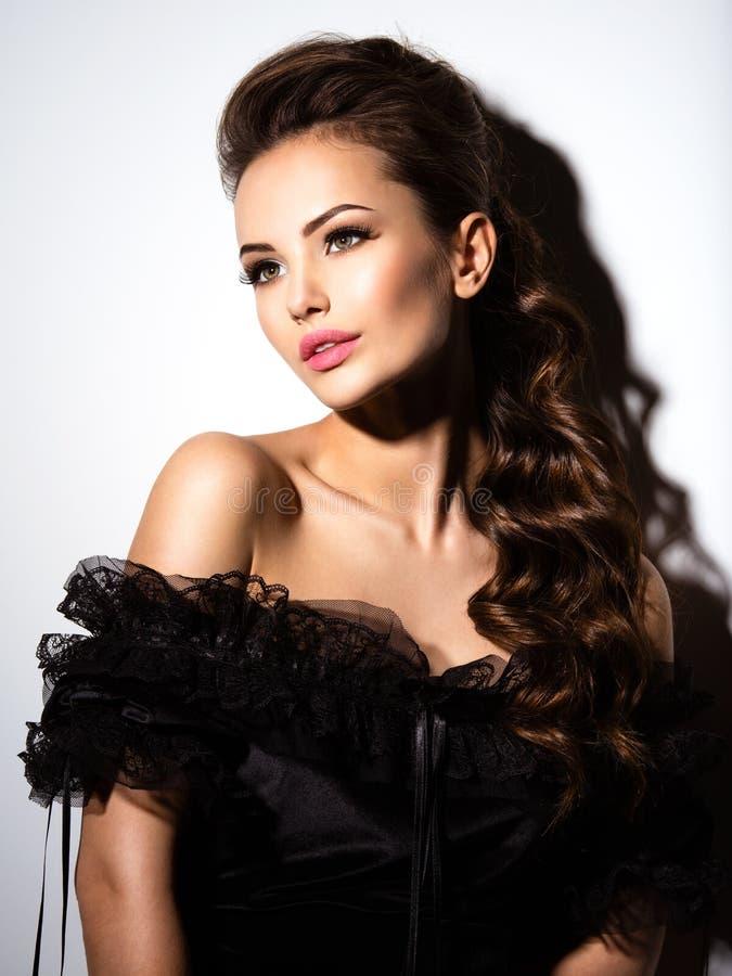 Красивая сторона молодой сексуальной девушки в черном платье стоковые изображения rf