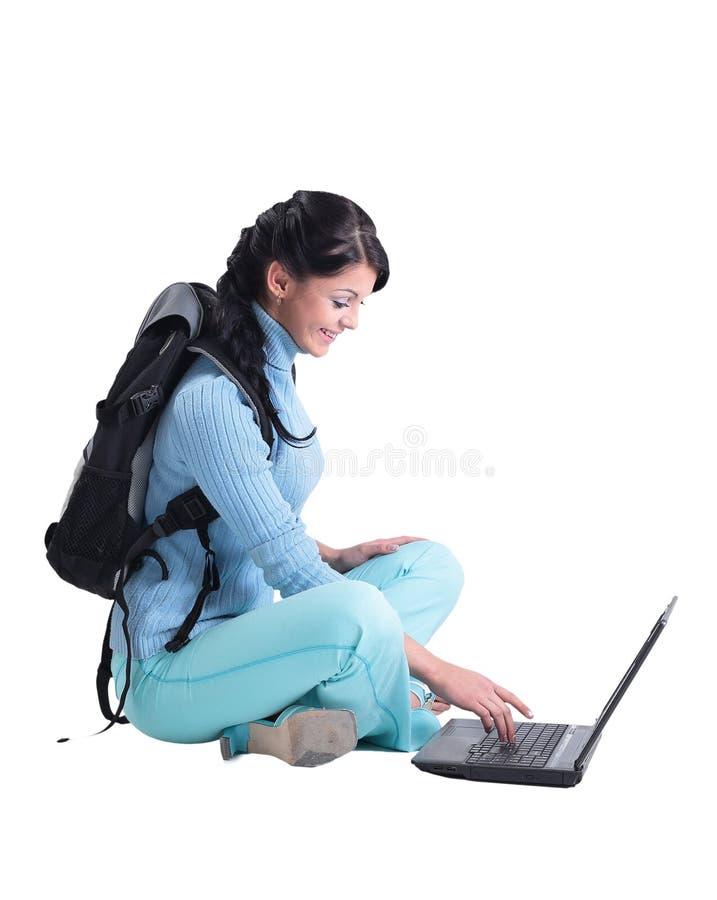 Красивая студентка работая на компьтер-книжке изолированной на белизне стоковая фотография rf