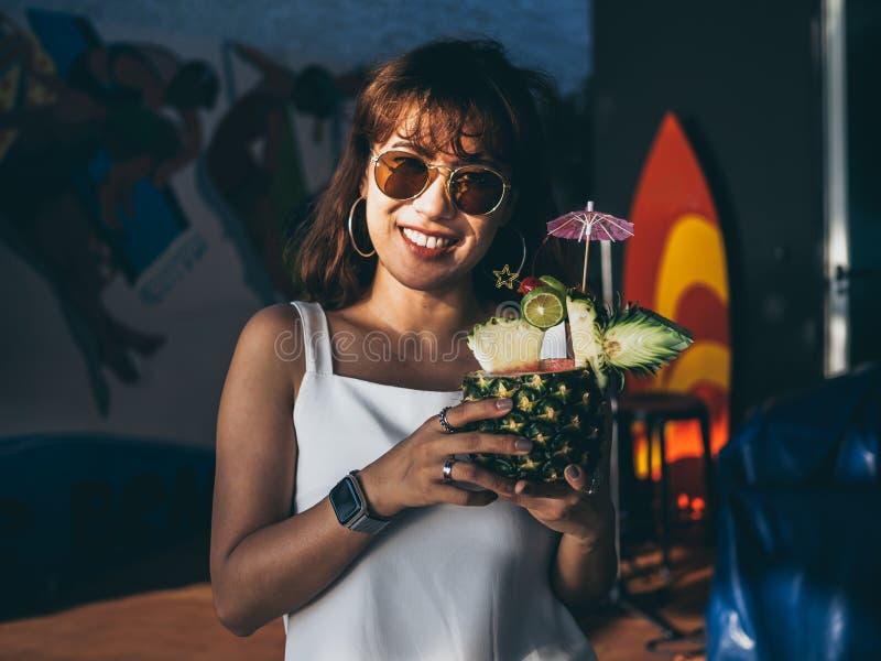 Красивая счастливая азиатская женщина нося белое безрукавное и солнечные очки держа коктейль сока ананаса летом стоковая фотография