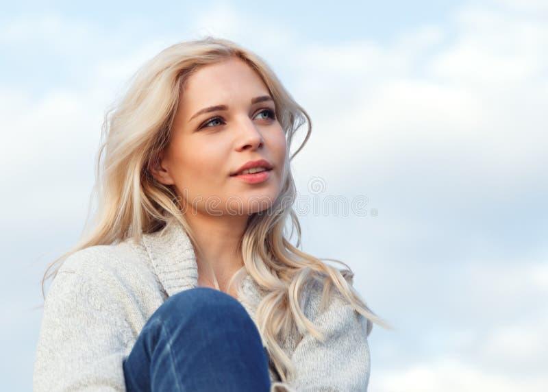 Красивая счастливая блондинка в сером свитере и джинсах усмехаясь против голубого неба Перемещение, отдых, концепция туризма стоковые фото