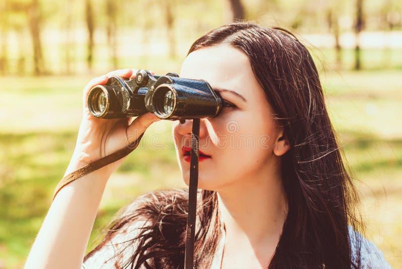 Красивая счастливая женщина брюнет наслаждаясь весной outdoors Она держа винтажные бинокли стоковая фотография