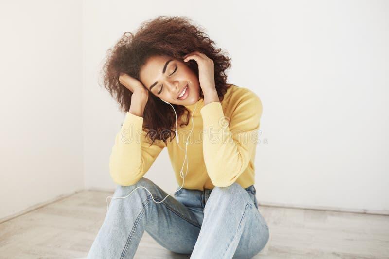Красивая счастливая молодая африканская темнокожая девушка при курчавый афро стиль причёсок нося желтый turtleneck и джинсы, усме стоковые изображения rf
