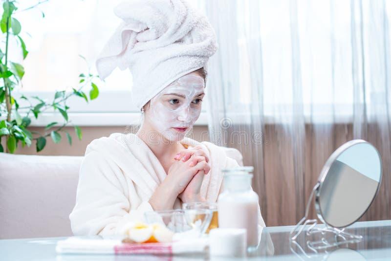 Красивая счастливая молодая женщина с естественной косметической маской на стороне Забота и процедуры спа кожи концепции дома стоковые фотографии rf