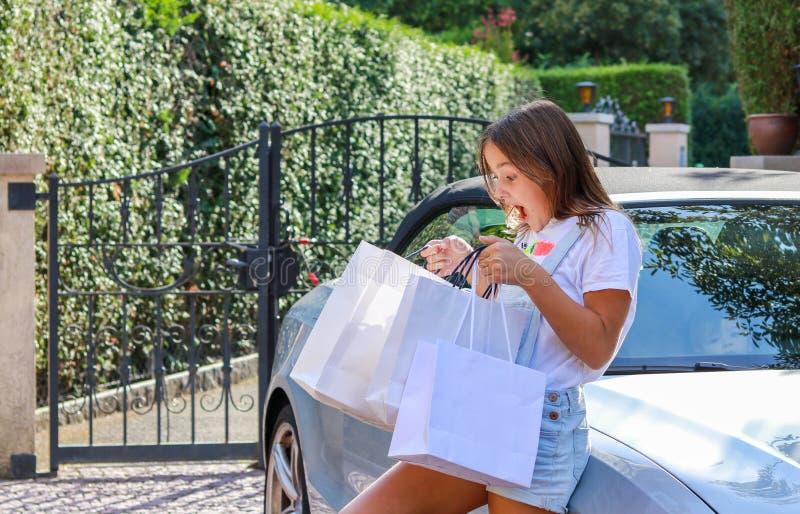 Красивая счастливая удивленная девушка preteen оставаясь на автомобиле при хозяйственные сумки смотря в возбужденную сумку стоковая фотография rf