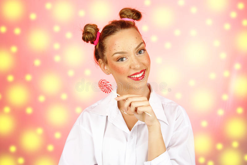 Красивая счастливая девушка при веснушки держа и есть леденец на палочке конфеты помадок с выражением лица стоковое изображение