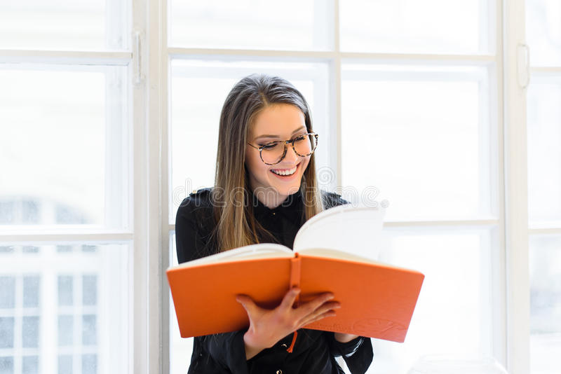 Красивая счастливая девушка студента в книге чтения стекел на windowsill стоковое изображение