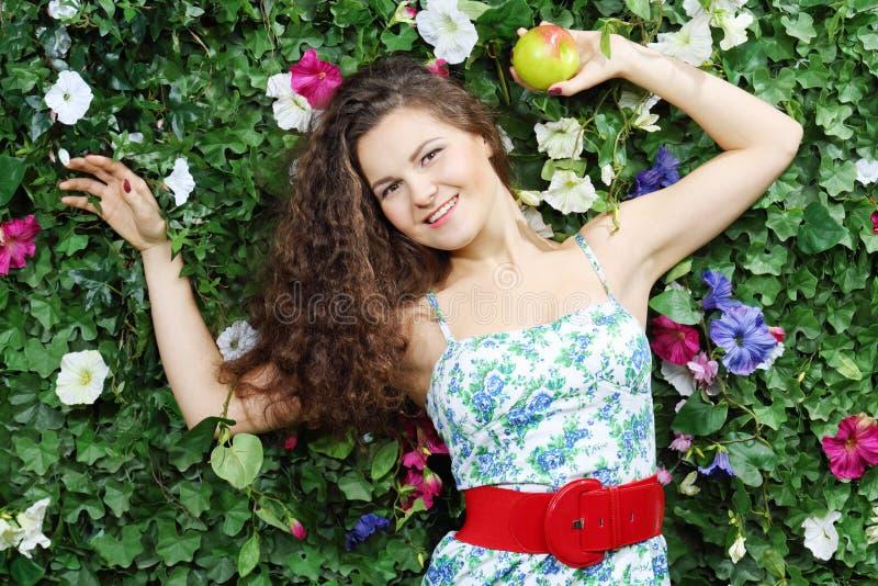Красивая счастливая женщина с яблоком рядом с зеленой изгородью стоковые фотографии rf
