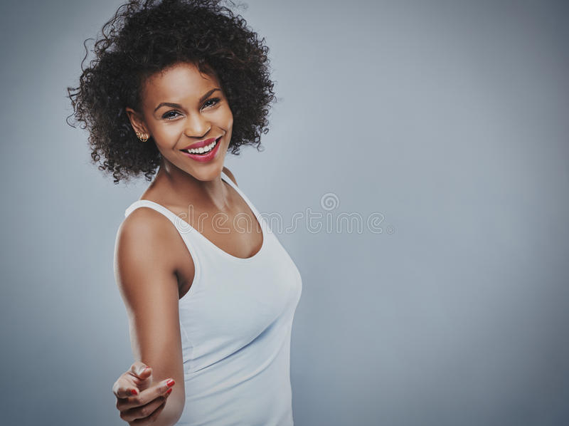 Красивая счастливая женщина танцуя над серой предпосылкой стоковые фото