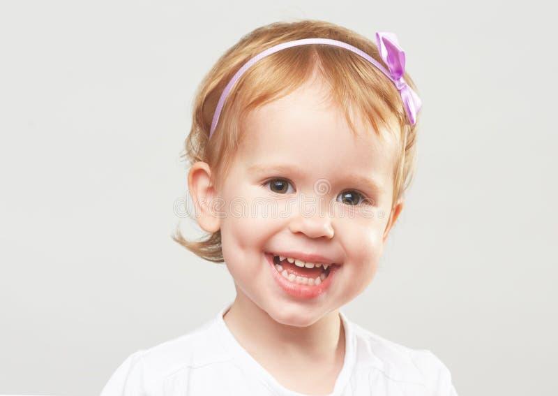 Красивая счастливая маленькая девочка смеясь над и усмехаясь на серой предпосылке стоковые фото
