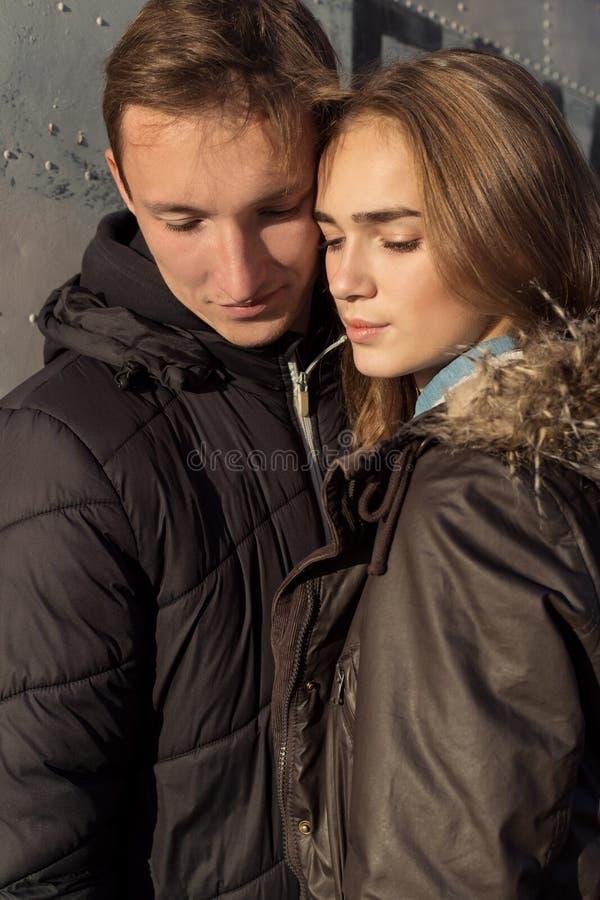 Красивая счастливая милая пара в влюбленности обнимает и глаза закрытые на заходе солнца около стены падают на теплый вечер стоковая фотография