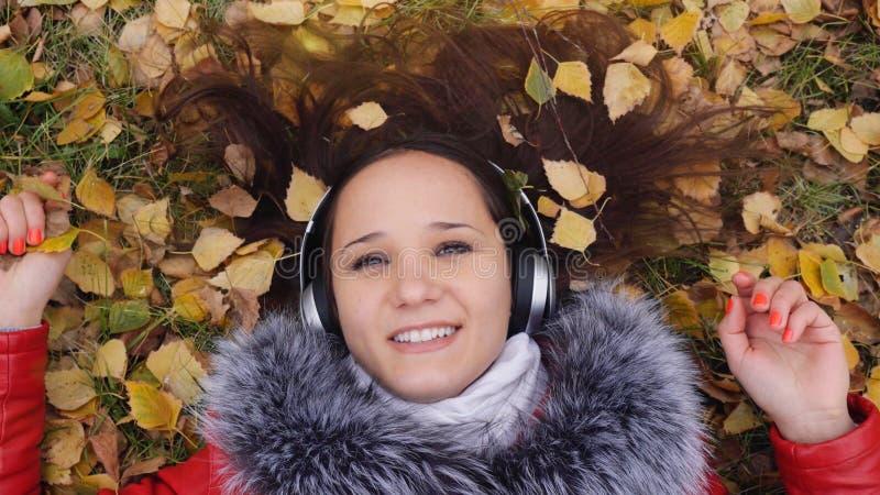 Красивая счастливая молодая женщина при наушники лежа на листьях осени слушая к музыке Сезон, технология и люди стоковые изображения rf