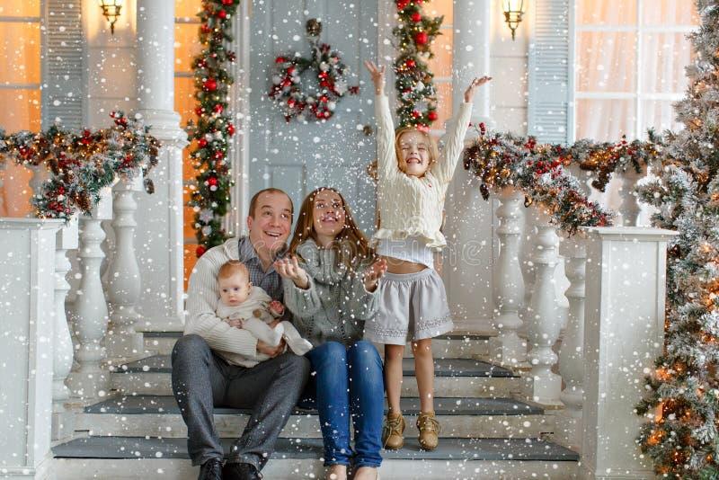 Красивая счастливая семья с маленькими девочками в усаживании свитера knit стоковая фотография
