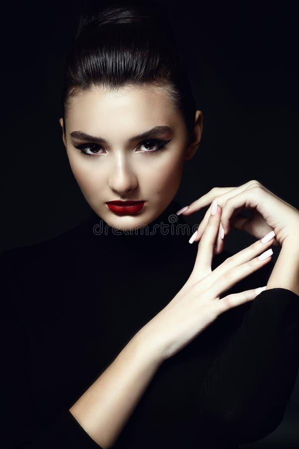 Красивая темная с волосами модель с провокационным составляет и волосы выскоблили назад в высокую плюшку слитую на черной предпос стоковые фотографии rf