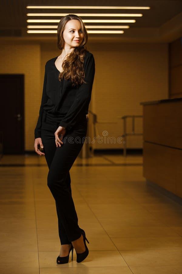 Красивая темн-с волосами женщина стоя внутри и сексуальная смотря в сторону стоковая фотография