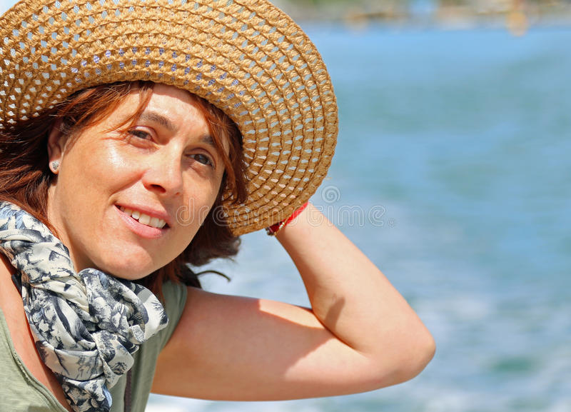 Красивая 40-ти летняя женщина с соломенной шляпой во время круиза стоковое фото
