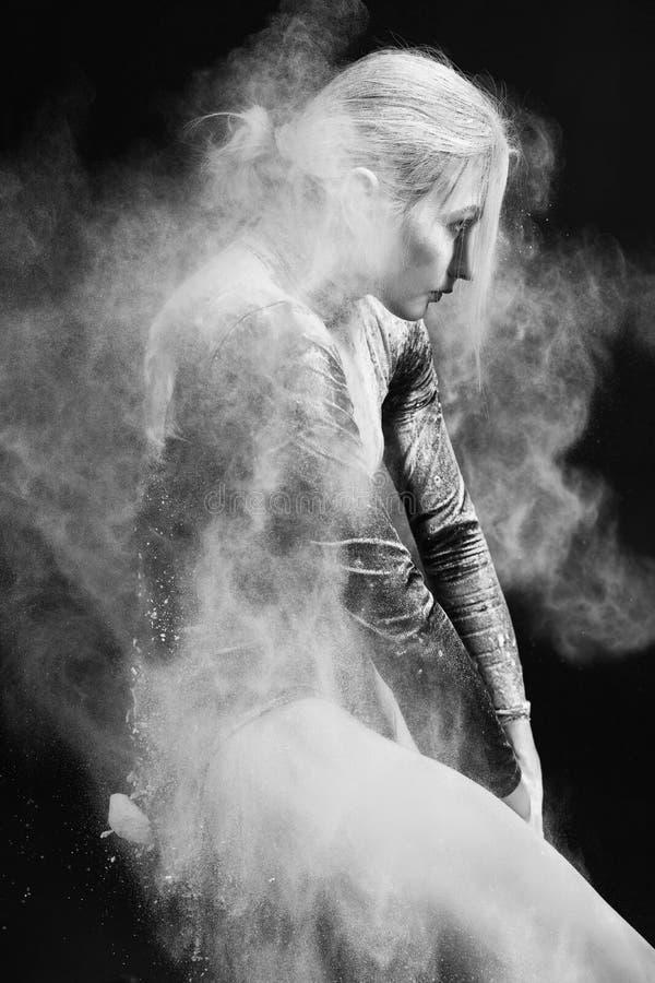 Красивая тонкая девушка нося гимнастический bodysuit покрытый с облаками белых танцев летая порошка на темной предпосылке стоковые изображения rf
