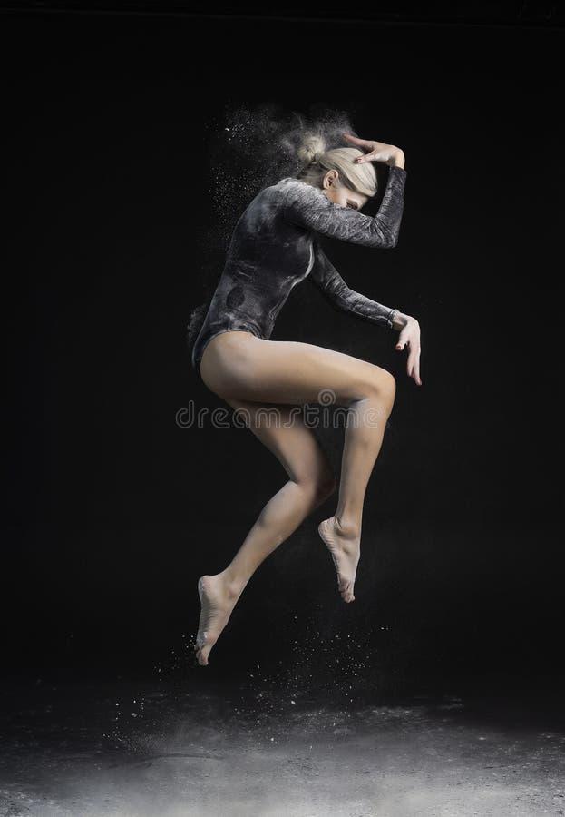 Красивая тонкая девушка нося черный гимнастический bodysuit покрытый с облаками белых скачек летая порошка танцуя на темноте стоковое фото rf
