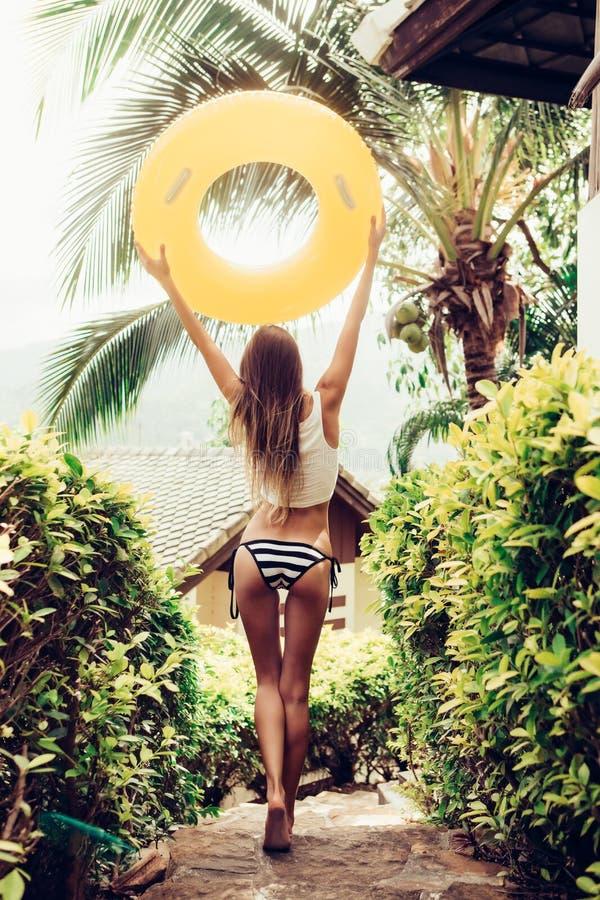 Красивая тонкая девушка в сексуальном striped бикини идя вниз с stai стоковое фото