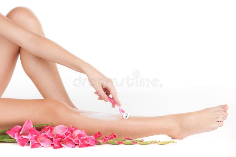 Красивая тонкая женщина брея ноги стоковое изображение