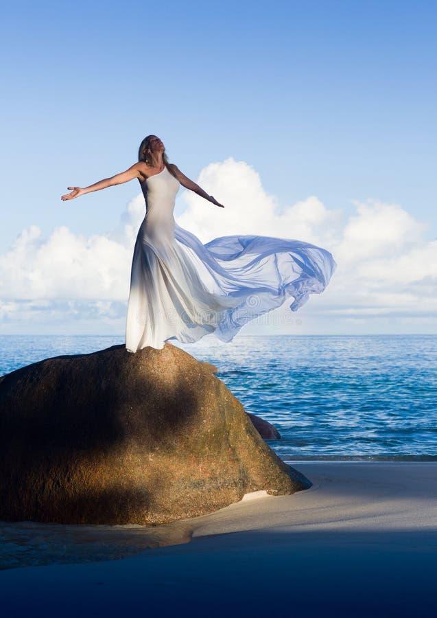 Красивая тонкая женщина в белом платье летая на песчаном пляже стоковые изображения rf