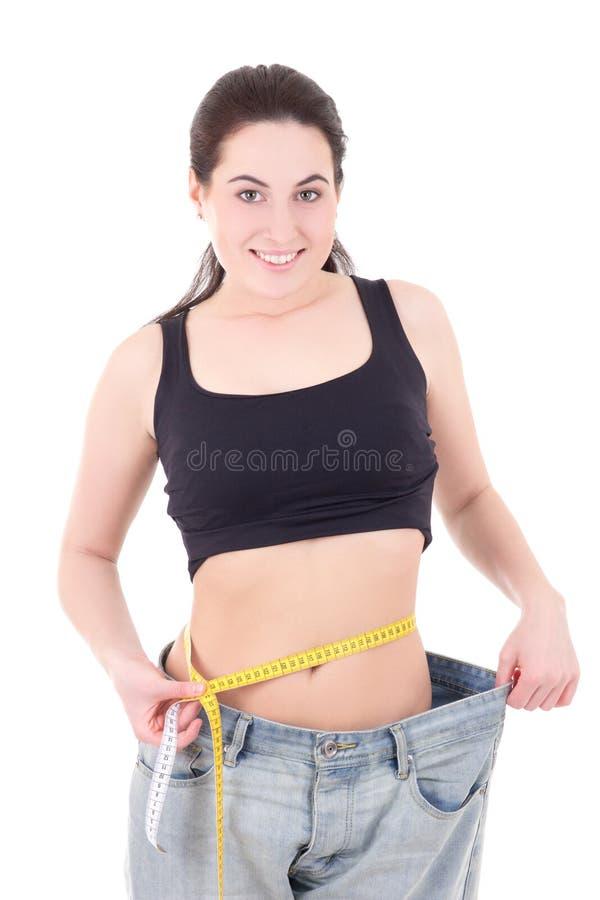 Красивая тонкая женщина в больших джинсах при измеряя изолированная лента стоковая фотография
