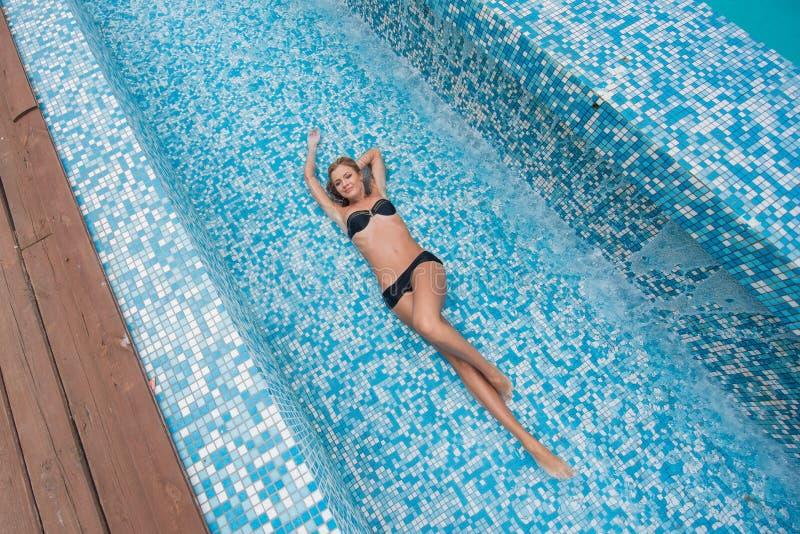 Красивая тонкая сексуальная белокурая девушка в черном купальном костюме кладет в бассейн стоковые фотографии rf