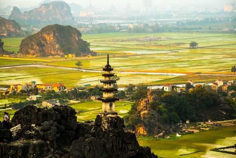 Красивая точка зрения ландшафта захода солнца с белым stupa от вершины горы пещеры M.U.A., Ninh Binh, Tam Coc, Вьетнамом стоковая фотография