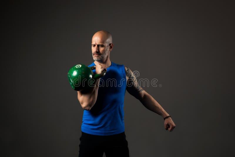 Красивая тренировка спортсмена с kettlebell, предпосылкой студии стоковое изображение rf