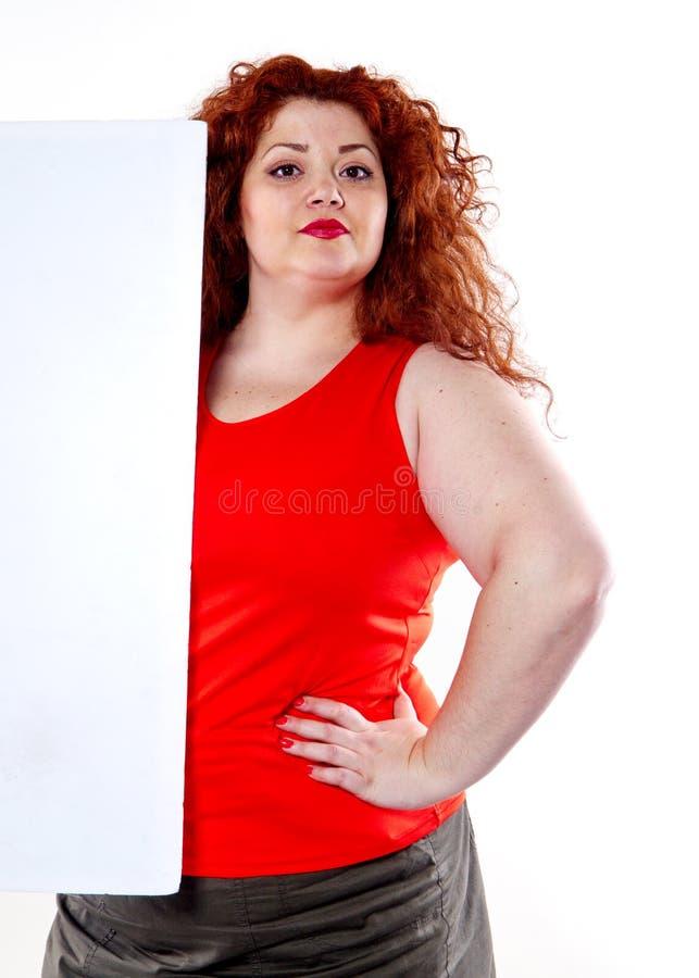 красивая тучная, большая женщина чувственности с красной губной помадой и при красные футболки держа белое bilboard стоковое изображение rf