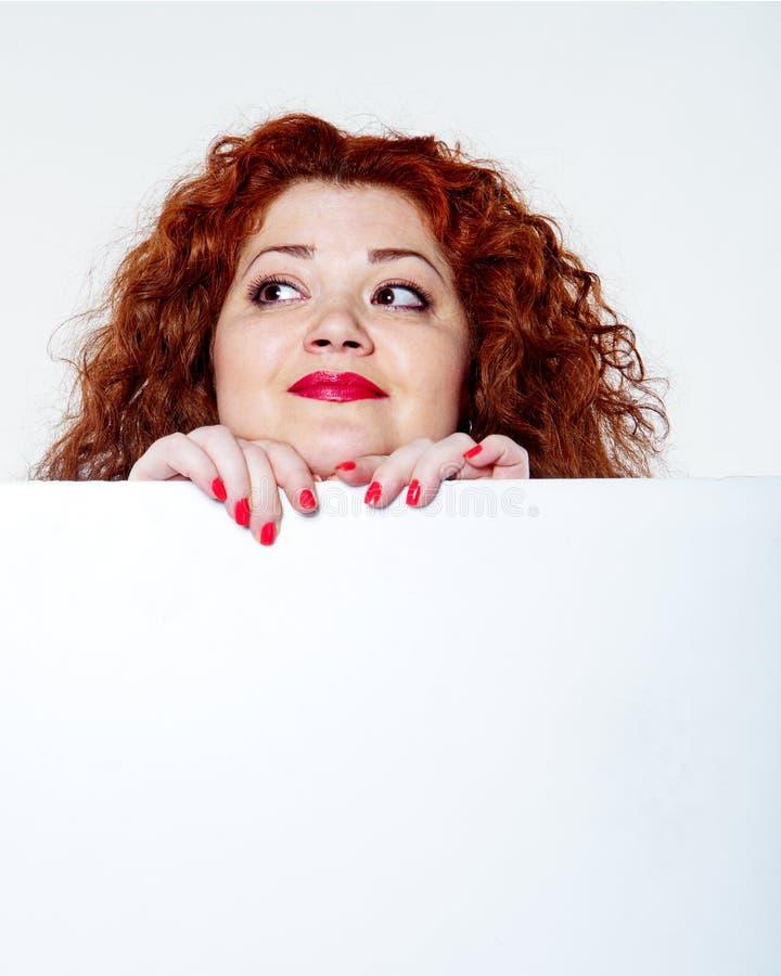 красивая тучная, большая женщина чувственности с красной губной помадой и при красные футболки держа белое bilboard стоковые изображения rf
