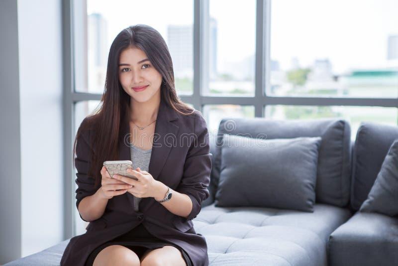 красивая уверенная азиатская молодая бизнес-леди усмехаясь и используя смартфон распологая на софу, на окне в предпосылке города  стоковые фотографии rf