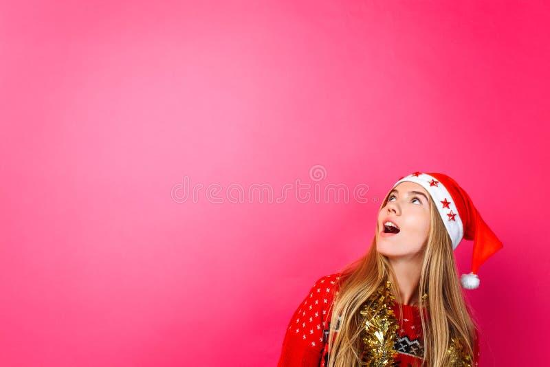 Красивая удивленная девушка в шляпе Санта, с сусалью на ее шеи, взгляды на пустом космосе экземпляра на красной предпосылке стоковые фото