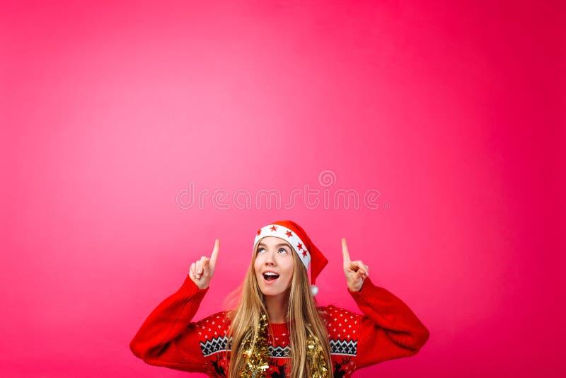 Красивая удивленная девушка в шляпе Санта, с сусалью на ее шеи указывая пальцы вверх и показывая пустой космос экземпляра на крас стоковое фото