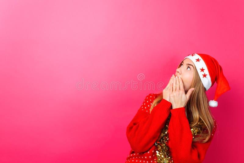 Красивая удивленная девушка в шляпе Санта, с сусалью на ее шеи, услаженной с что-то, смотрит пустой космос экземпляра на красном  стоковое фото