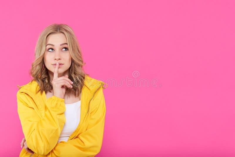 Красивая ультрамодная девушка в красочных одеждах глубоко в мыслях, смотря вверх с пальцем на губах привлекательные детеныши женщ стоковые изображения rf