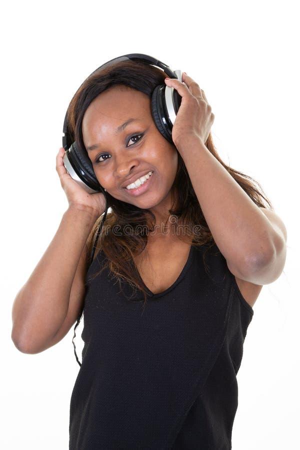 Красивая усмехаясь американская африканская женщина с наслаждаться наушников слушает музыка стоковые фотографии rf