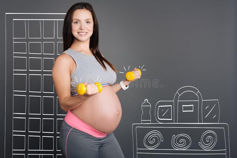 Красивая усмехаясь беременная женщина делая тренировки спорта стоковое изображение