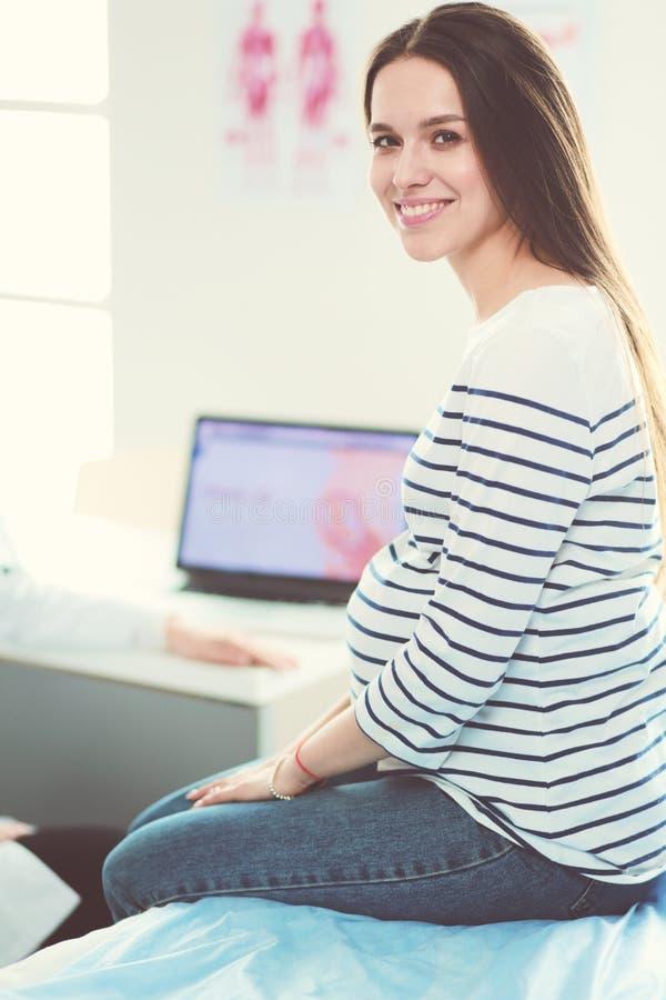Красивая усмехаясь беременная женщина с доктором на больнице стоковое изображение
