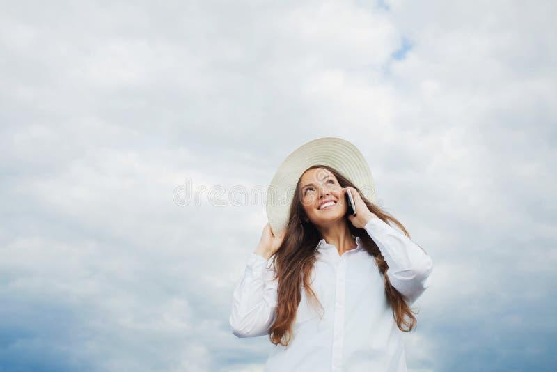 Красивая усмехаясь девушка в белой шляпе с широким brim говоря на телефоне на предпосылке облаков шторма Скопируйте космос для те стоковые изображения