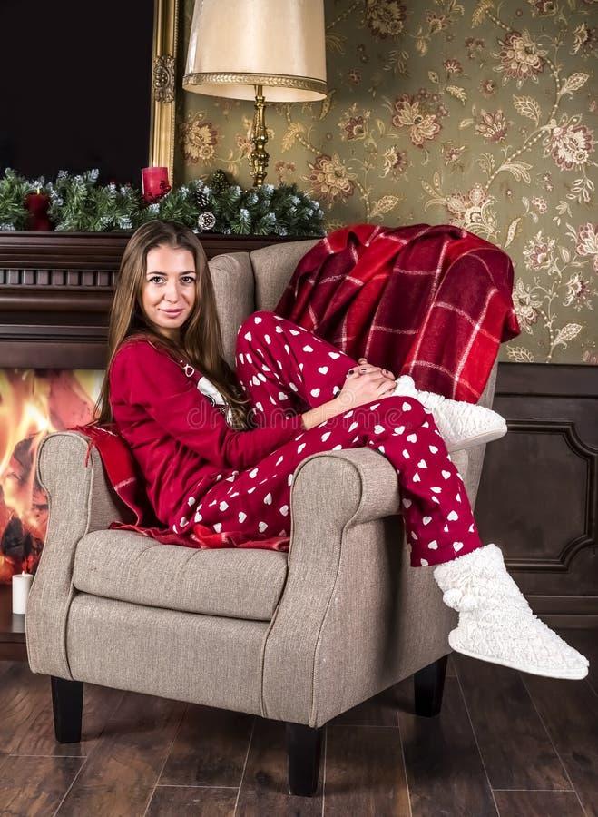 Красивая усмехаясь девушка в красных пижамах одежд дома рождества и белых домашних ботинках сидит в стуле на фоне th стоковая фотография rf