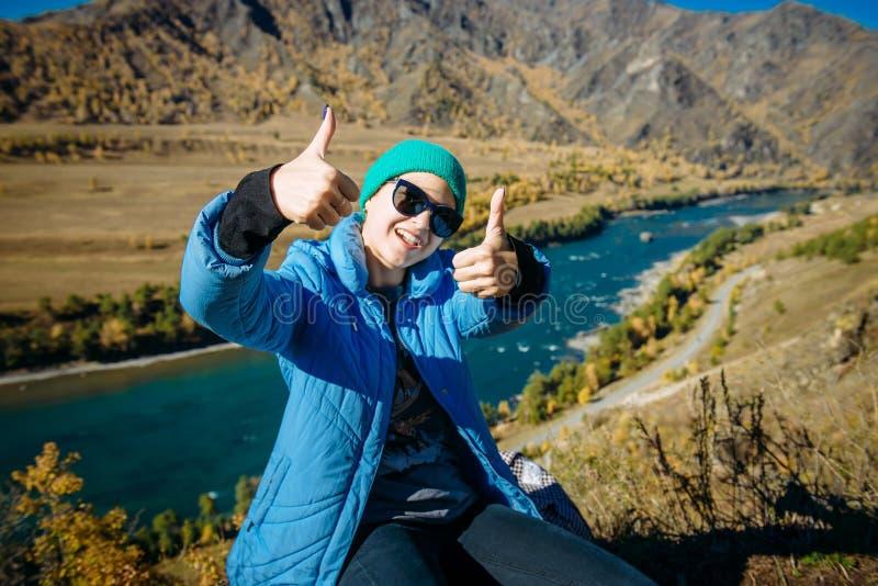 Красивая усмехаясь девушка в солнечных очках показывает большие пальцы руки вверх, сидящ на холме, наслаждаясь днем осени в горах стоковое изображение rf