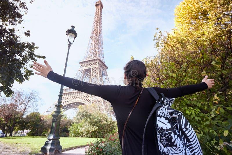 Красивая усмехаясь девушка представляя с оружиями широко открытыми на предпосылке Эйфелевой башни Париж, Чемпион de Марс стоковое изображение rf