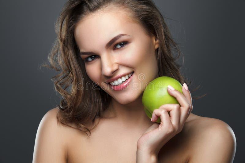 Красивая усмехаясь девушка брюнет держа зеленое яблоко стоковые изображения