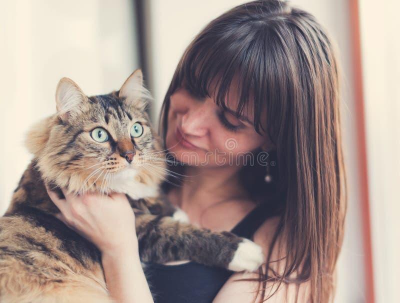 Красивая усмехаясь девушка брюнет и ее кот имбиря стоковые изображения