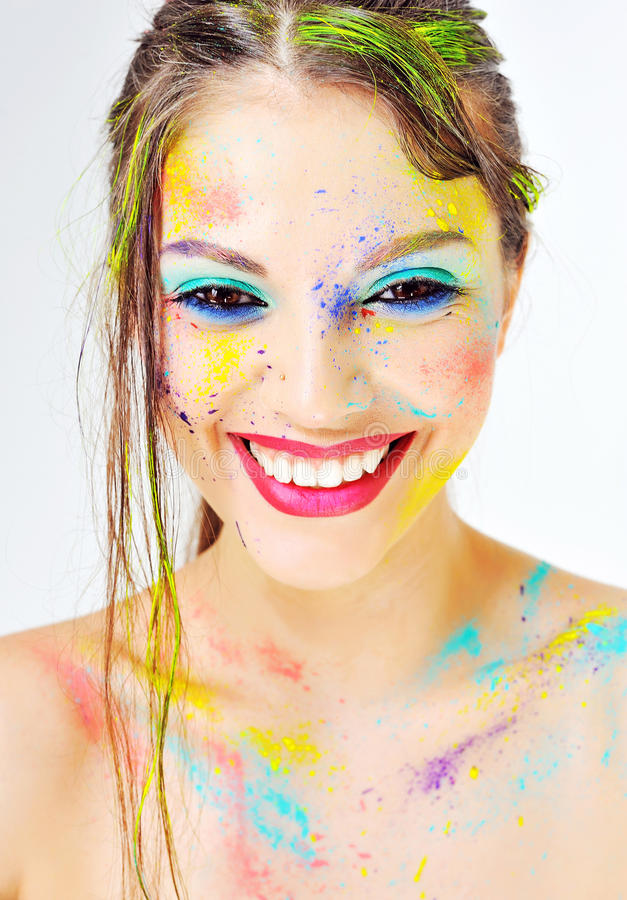 Красивая усмехаясь девушка с красочной краской брызгает на стороне стоковая фотография rf